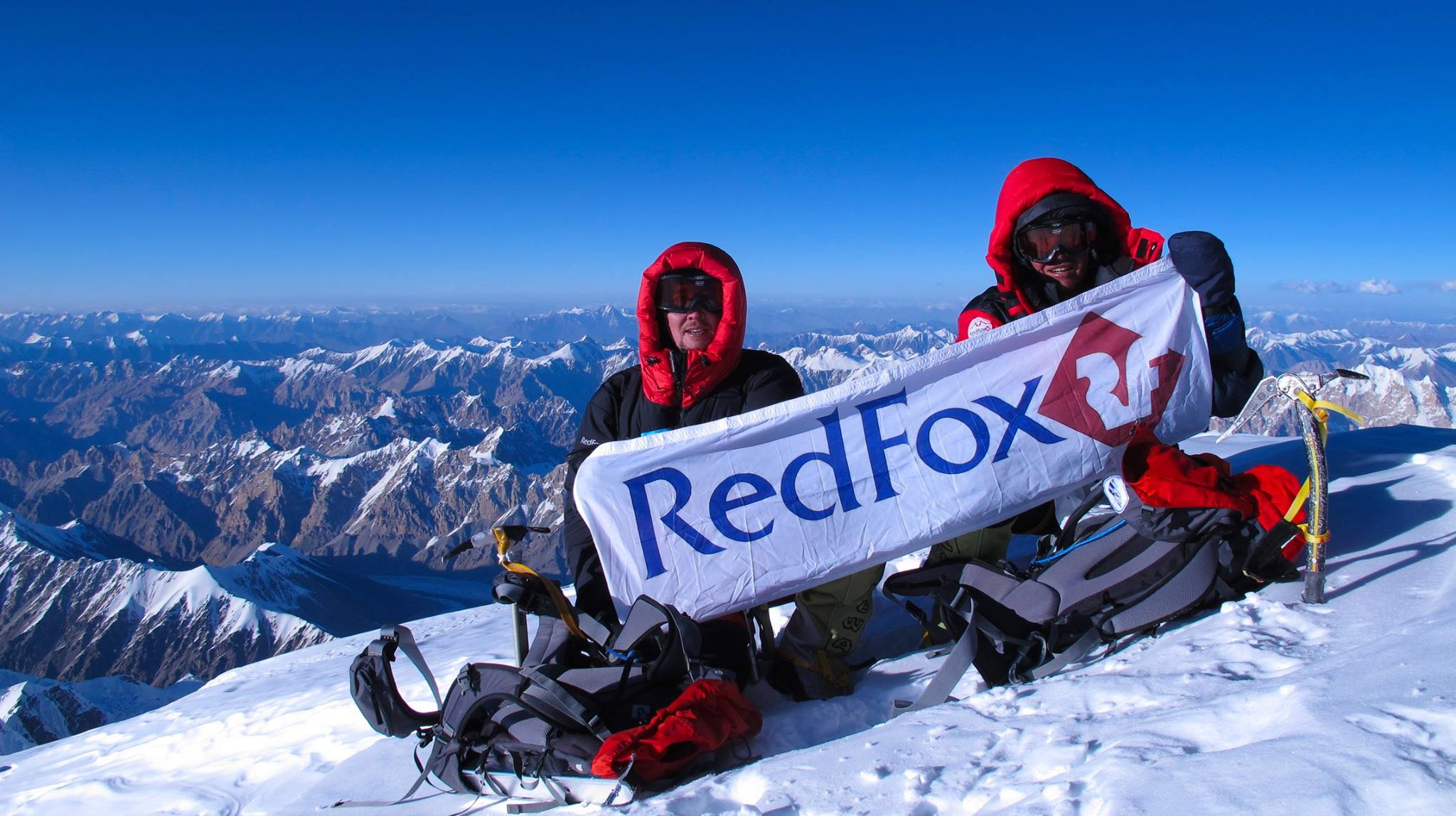 hikers with red fox banner on top of a mountain