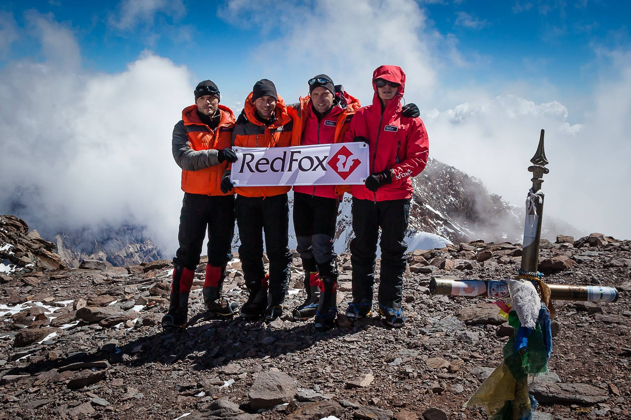 four hikers with red fox banner at summit of mountain
